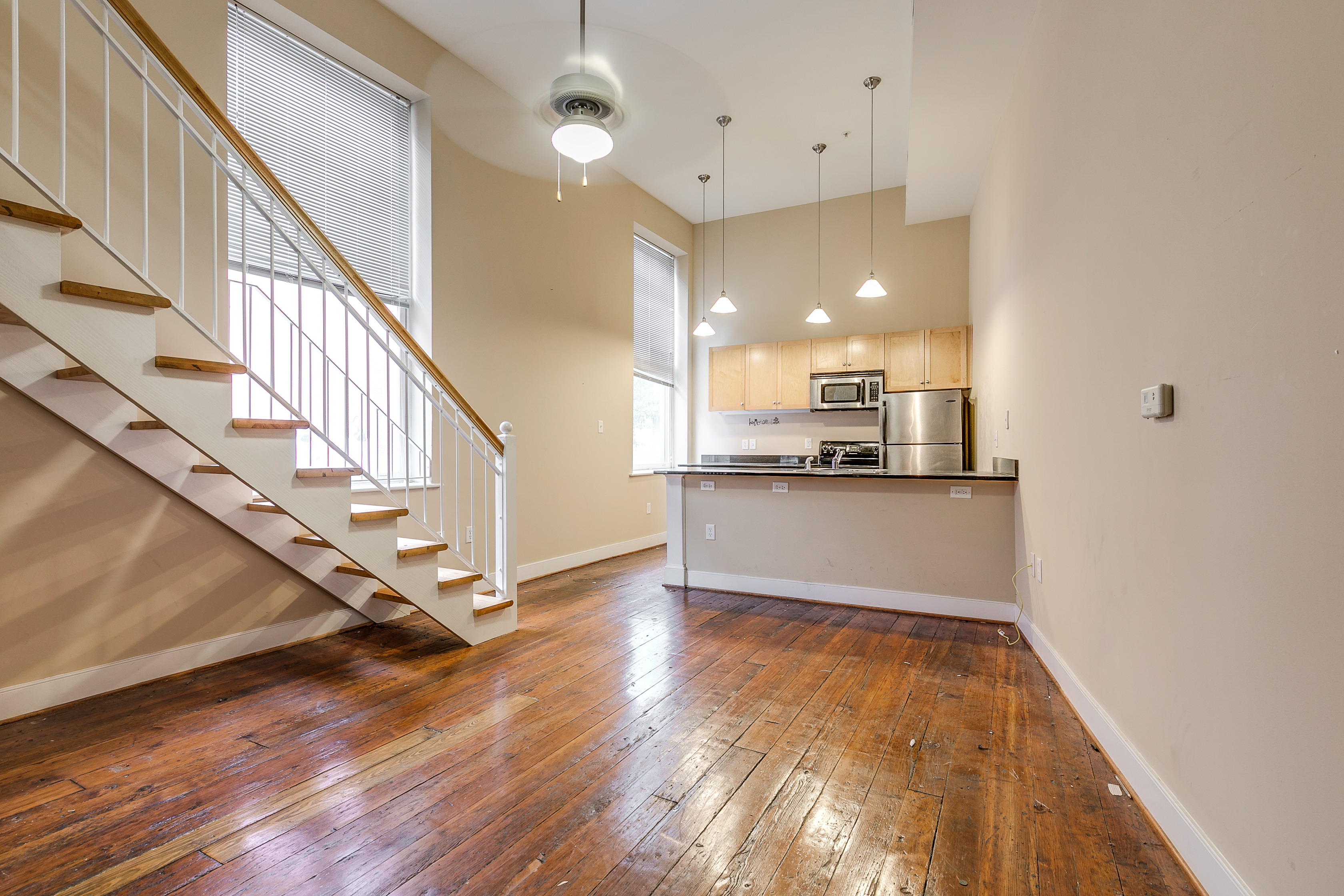 High Ceilings, Kitchen Counter Seating And Staircase To Upper Loft